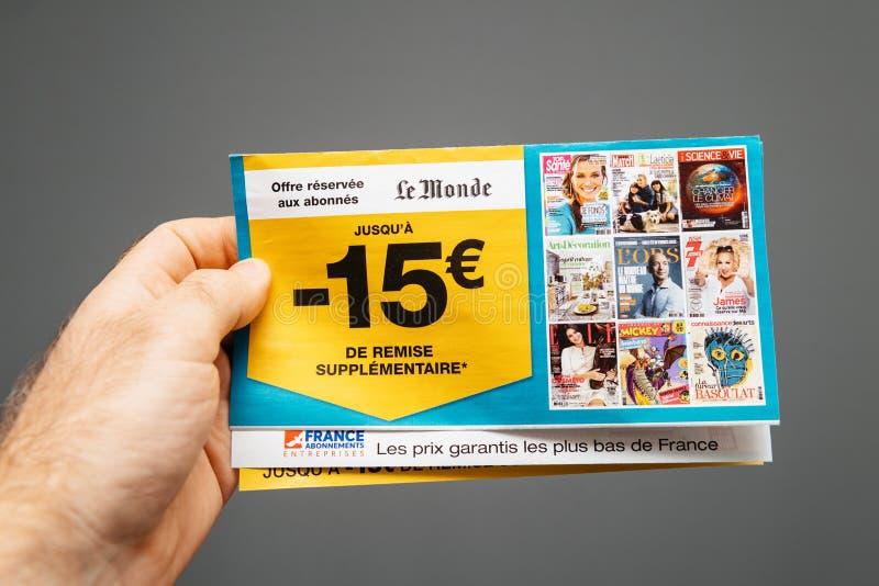 M?o masculina que guarda a oferta especial de Le Monde para subscritores imagem de stock