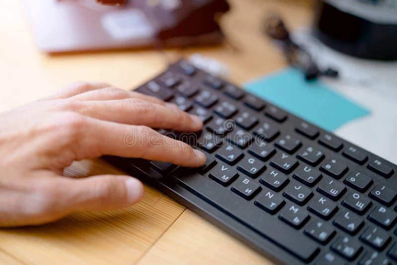 M?o no teclado de computador Close-up ensolarado lugar de trabalho imagem de stock royalty free