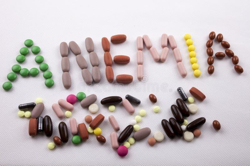 M?o que escreve o conceito dos cuidados m?dicos escrito com palavra ANEMIA da c?psula das drogas dos comprimidos no fundo isolado imagens de stock