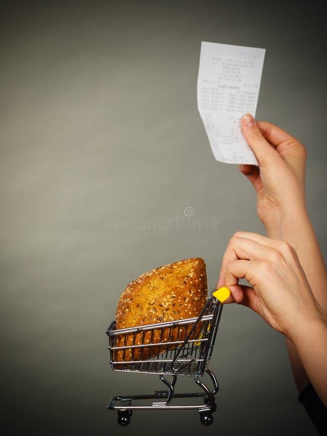 M?o que guarda o carrinho de compras com p?o e conta imagens de stock