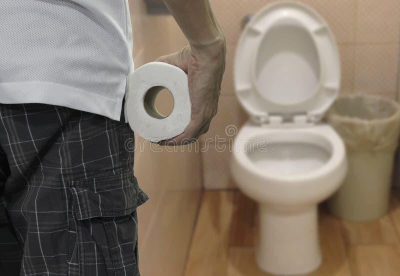 M?o que guarda o rolo do papel higi?nico e que incorpora o toalete imagens de stock royalty free