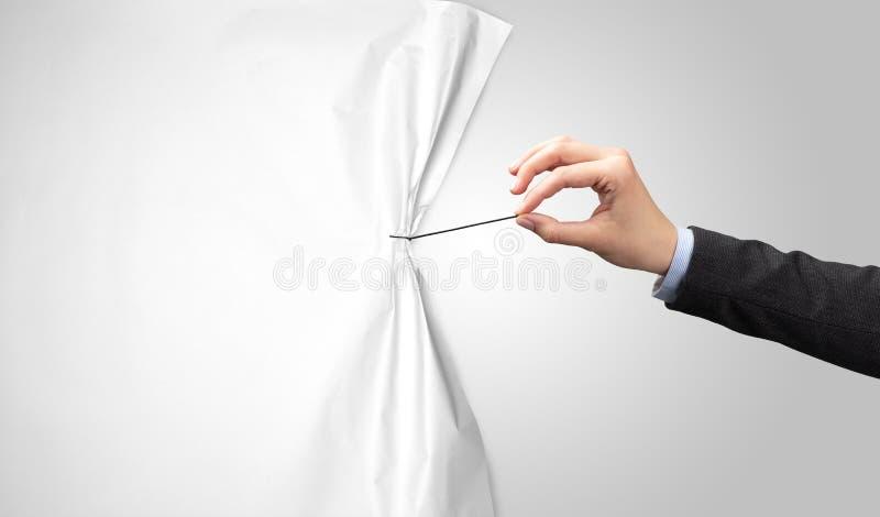 M?o que puxa a cortina do Livro Branco imagens de stock royalty free