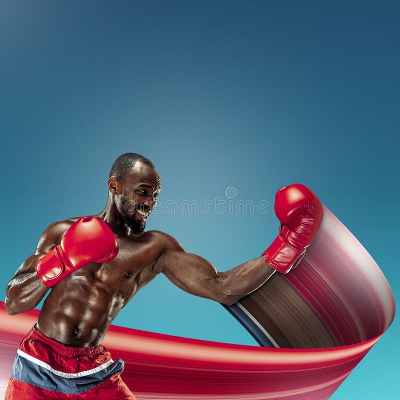 M?oda afroameryka?ska atleta trenuje nad b??kitnym t?em zdjęcie royalty free