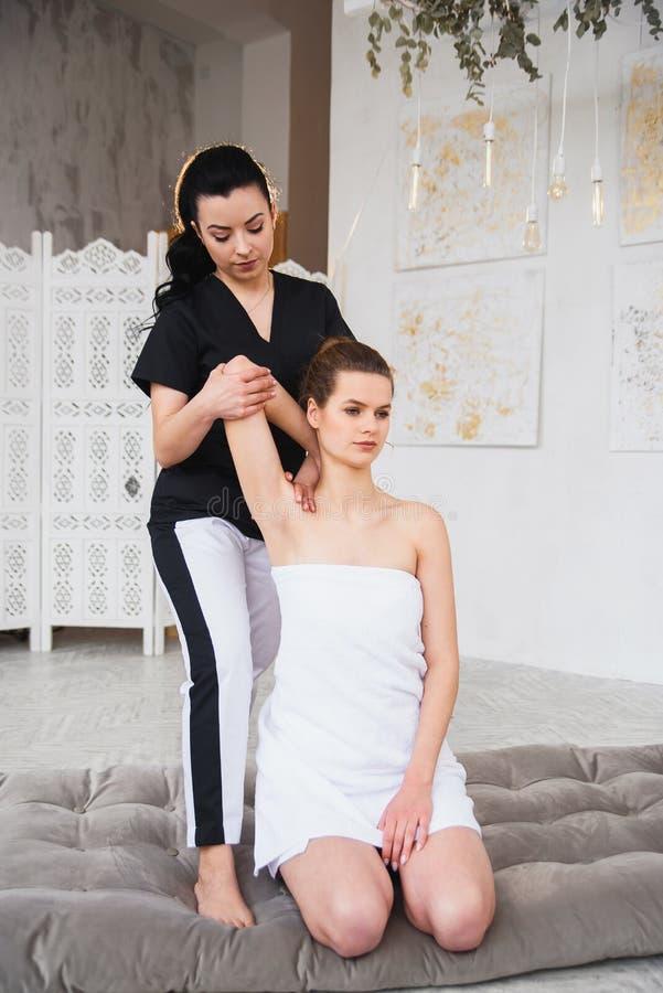 M?oda atrakcyjna kobieta na traktowanie procedurze podczas gdy ?e?skiego terapeuty streching r?ki patint Dolly strza? obrazy stock