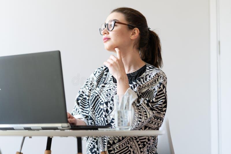 M?oda atrakcyjna kobieta pracuje na laptopie w nowo?ytnych jaskrawych mieszkaniach fotografia royalty free