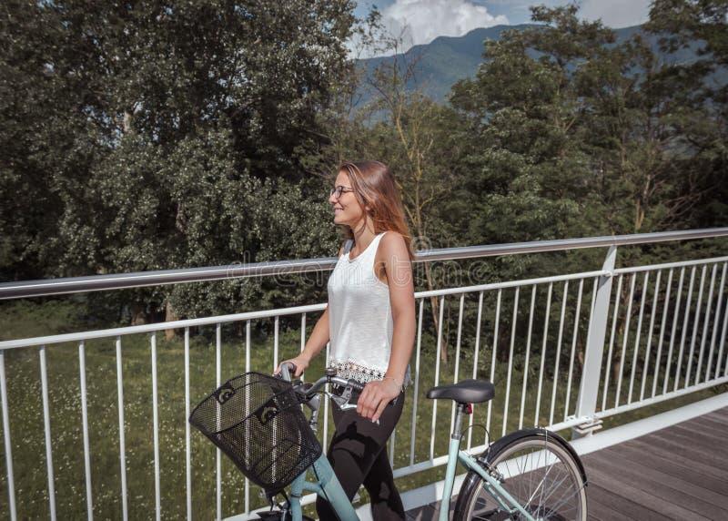 M?oda atrakcyjna kobieta z bicyklem na mo?cie zdjęcie stock