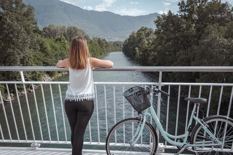 M?oda atrakcyjna kobieta z bicyklem na mo?cie zdjęcie royalty free
