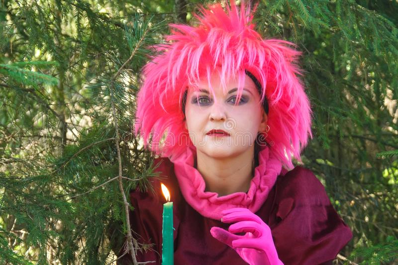 M?oda czarownica w purpur ubraniach z ?wieczk? w jego r?ce w lesie obraz stock