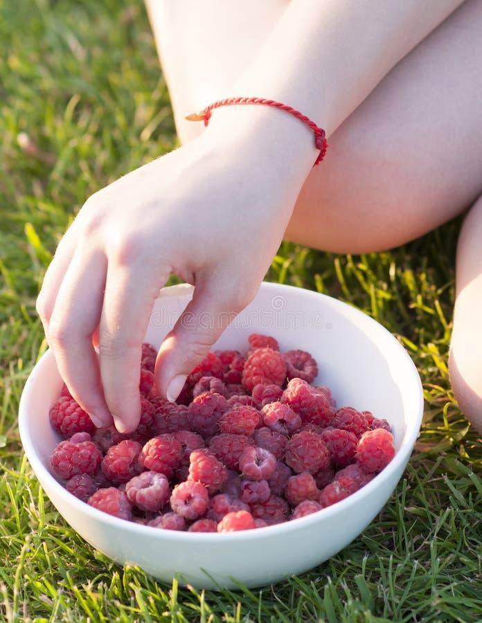 M?oda dziewczyna trzyma talerza malinki, siedzi na zielonej trawie, lato, deser zdjęcie stock