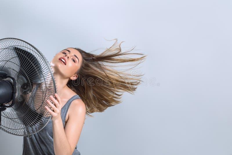M?oda kobieta cieszy si? ch?odno wiatr od elektrycznego fan obraz stock