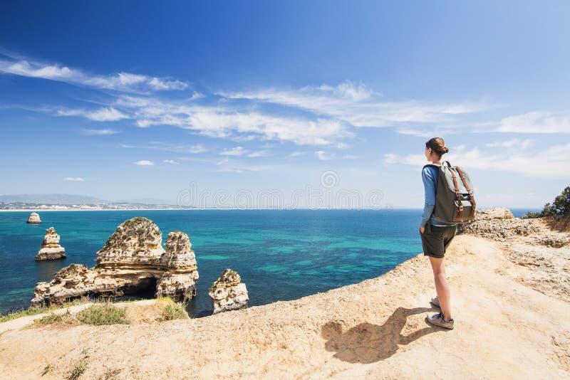 M?oda kobieta podr??nik patrzeje morze w Lagos miasteczku, Algarve region, Portugalia podr??y i aktywnego stylu ?ycia poj?cie zdjęcie royalty free