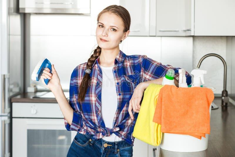 M?oda kobieta robi czy?ci? w domu, myje kuchni? Forsuje z ?achmanami i kolor ? fotografia royalty free