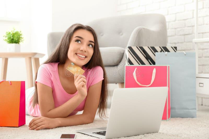 M?oda kobieta robi zakupy online z kredytow? kart? i laptopem w domu obraz royalty free