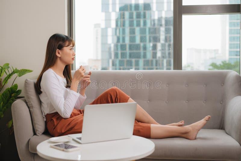 M?oda kobieta siedzi na kanapie przy wygodnym domowym wn?trzem w przypadkowych ubraniach Technologii i komunikaci poj?cie zdjęcie royalty free