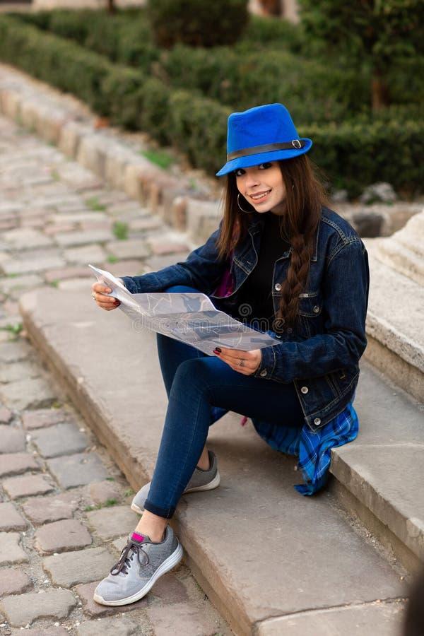 M?oda kobieta siedzi na schodkach w starym podw?rzu i czyta map?, Lviv, Ukraina fotografia royalty free