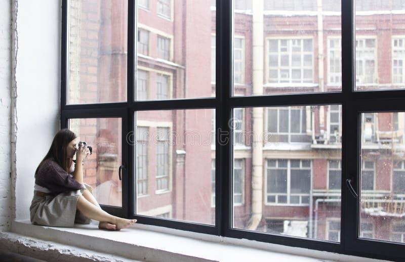 Download Młoda Kobieta Siedzi Na Windowsill Z Wielkimi Okno I Wp8lywy Zdjęcie Stock - Obraz złożonej z osoba, biznes: 106906906