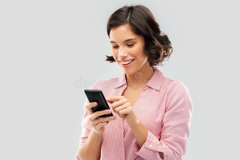 M?oda kobieta w pasiastym koszulowym u?ywa smartphone zdjęcie royalty free