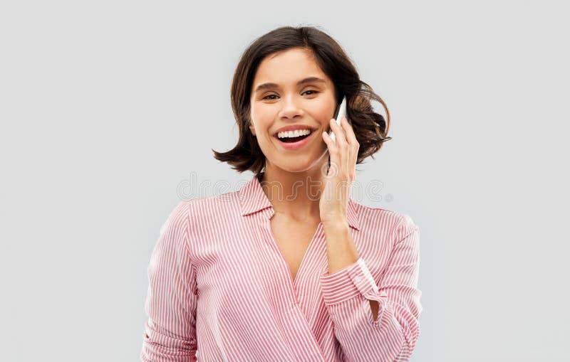 M?oda kobieta w pasiastym koszulowym wzywa smartphone zdjęcia stock