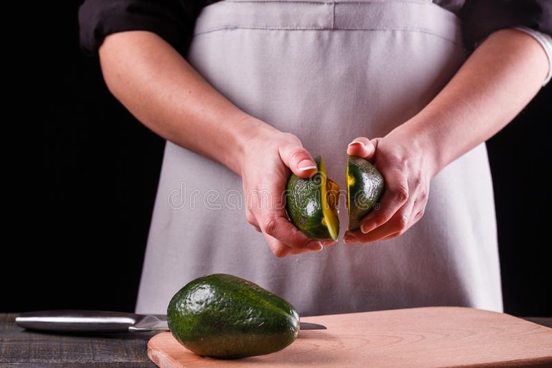 M?oda kobieta w szarym fartuchu ciie avocado na drewnianej tn?cej desce obrazy royalty free
