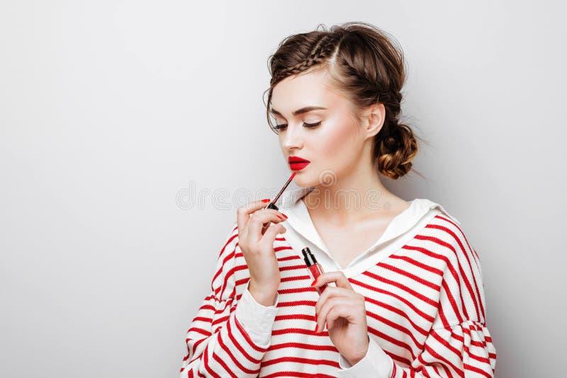 M?oda kobieta z czerwonymi wargami na dosy? emocjonalnej twarzy w eleganckiej sukni mienia makeup pomadce w studiu obraz royalty free