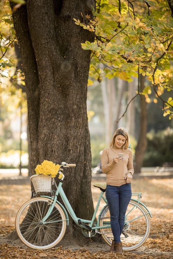 M?oda kobieta z rowerowym u?ywa smartphone w jesie? parku zdjęcia royalty free