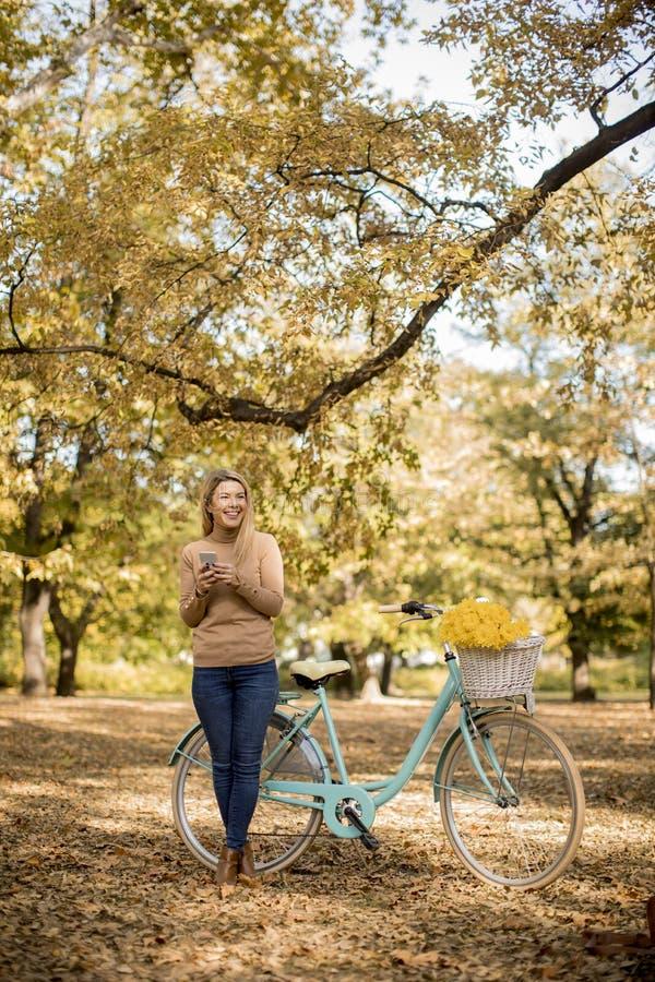 M?oda kobieta z rowerowym u?ywa smartphone w jesie? parku zdjęcie stock
