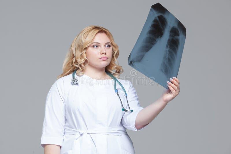M?oda kobiety lekarka patrzeje promieniowanie rentgenowskie obrazek p?uca fotografia stock