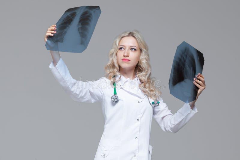 M?oda kobiety lekarka patrzeje promieniowanie rentgenowskie obrazek p?uca obraz stock