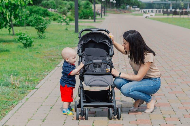 M?oda matka z dzieckiem obok spacerowicza chodzi w parku obraz royalty free
