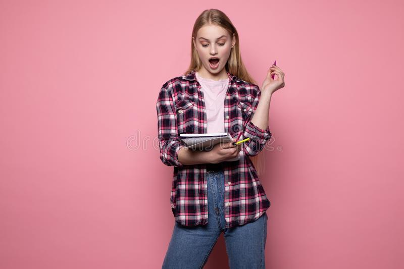 M?oda pi?kna blondynki dziewczyna w szkockiej kraty koszula z otwartym usta pokazuje Eureka znaka z jej pi?rem obrazy stock