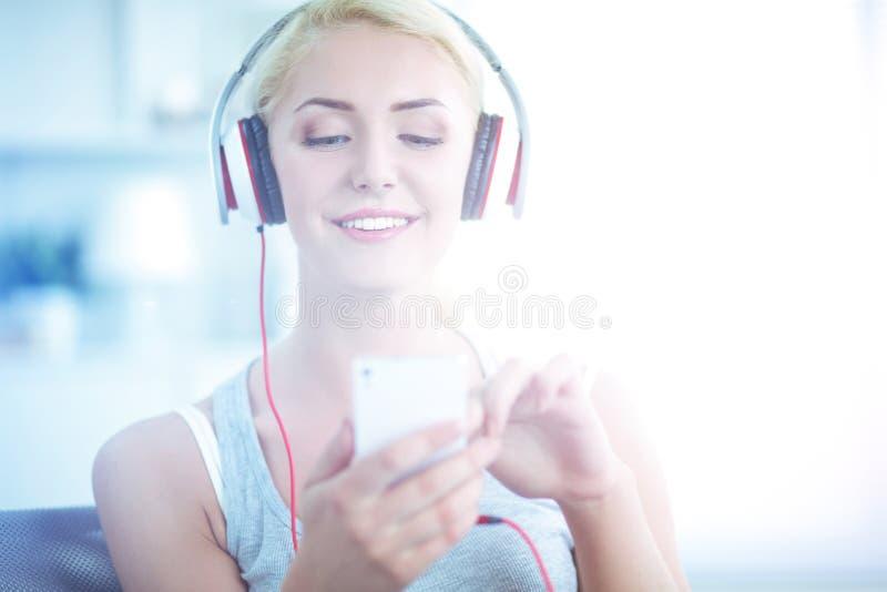 M?oda pi?kna kobieta siedzi na kanapie i s?uchaj?cej muzyce w domu zdjęcia royalty free