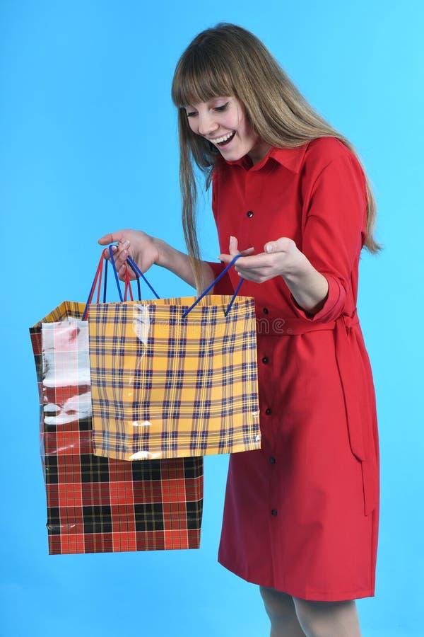 M?oda pi?kna kobieta w czerwieni sukni z kolor?w pakunkami zdjęcie stock