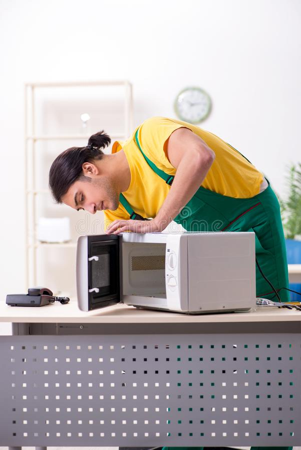 M?oda repairman naprawiania mikrofala w us?ugowym centre zdjęcie stock