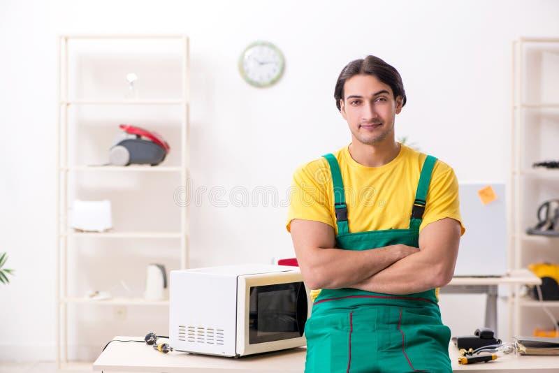 M?oda repairman naprawiania mikrofala w us?ugowym centre zdjęcie royalty free
