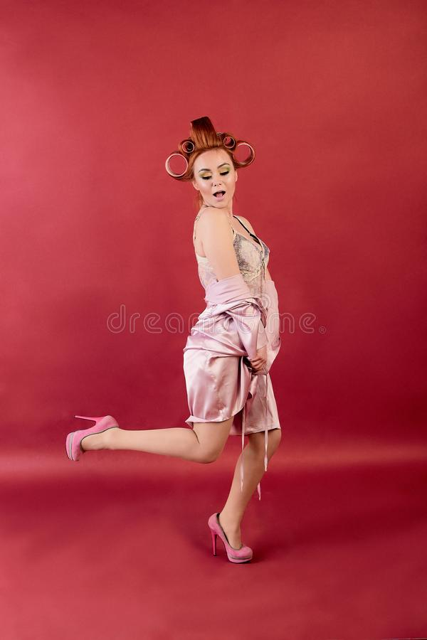 M?oda rudzielec kobieta z w?osianymi curlers ubiera? w neglige, peignoir, opatrunkowa toga pozuje na Burgundy tle obrazy stock