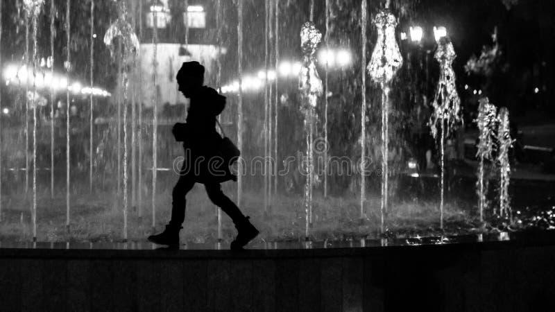 M?ode dziecko dziewczyna chodzi fontanny granic? Stylizowany jako czarny i bia?y sylwetka obraz stock