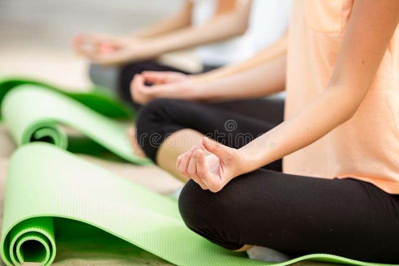 M?ode dziewczyny siedz? w lotosowych pozycjach na joga matach na piaskowatej pla?y na ciep?ym dniu obrazy stock