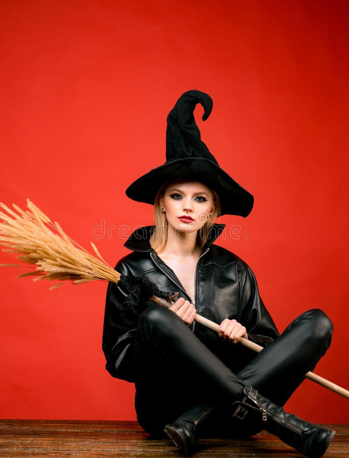 M?ode kobiety w czarnych czarownicy Halloween kostiumach na przyj?ciu nad czerwonym t?em Czarownicy miot?a lub broomstick poj?cie zdjęcia stock