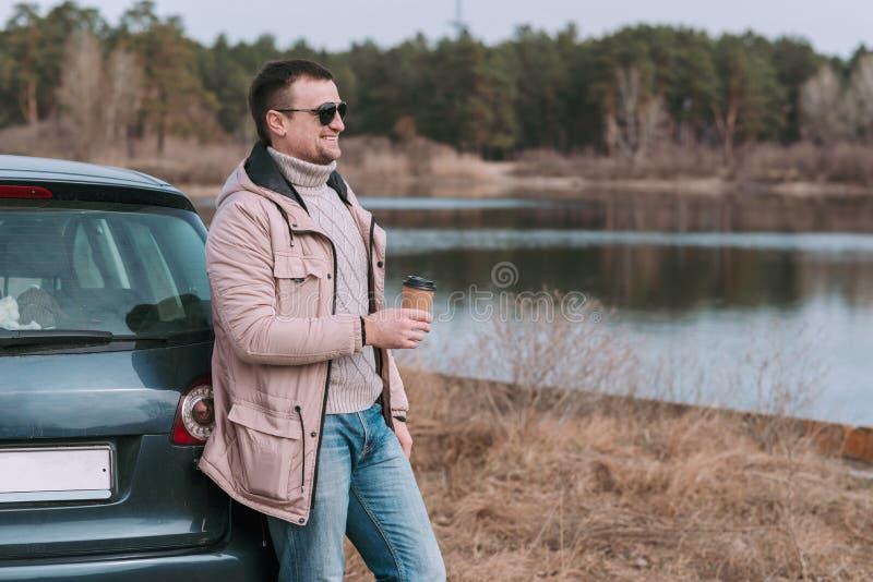 M?odego cz?owieka kierowca zatrzymuj?cy i odpoczywa z fili?anka kawy blisko samochodu podczas podr??y przerwy obraz royalty free