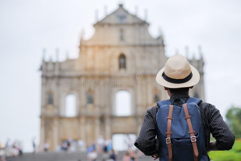 M?odego cz?owieka podr??ny backpacker z kapeluszem, Azjatycki modnisia podr??nik patrzeje ruiny St Paul, Historyczny Centre Macau zdjęcia royalty free