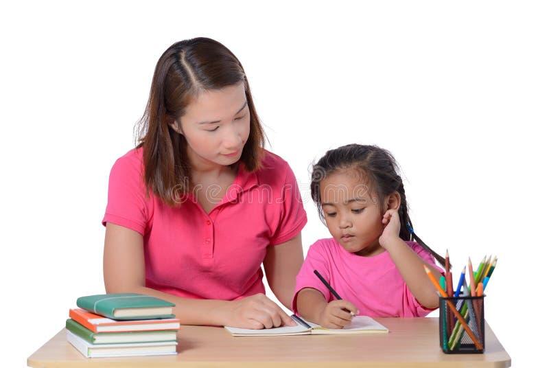 M?odego nauczyciela pomaga dziecko z pisa? lekcji odizolowywaj?cej na bia?ym tle obrazy stock