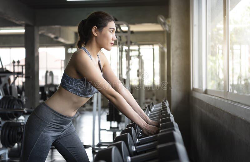 M?odej azjatykciej kobiety podno?ni dumbbells w gym zdrowy styl ?ycia i trening motywacji poj?cie zdjęcia royalty free