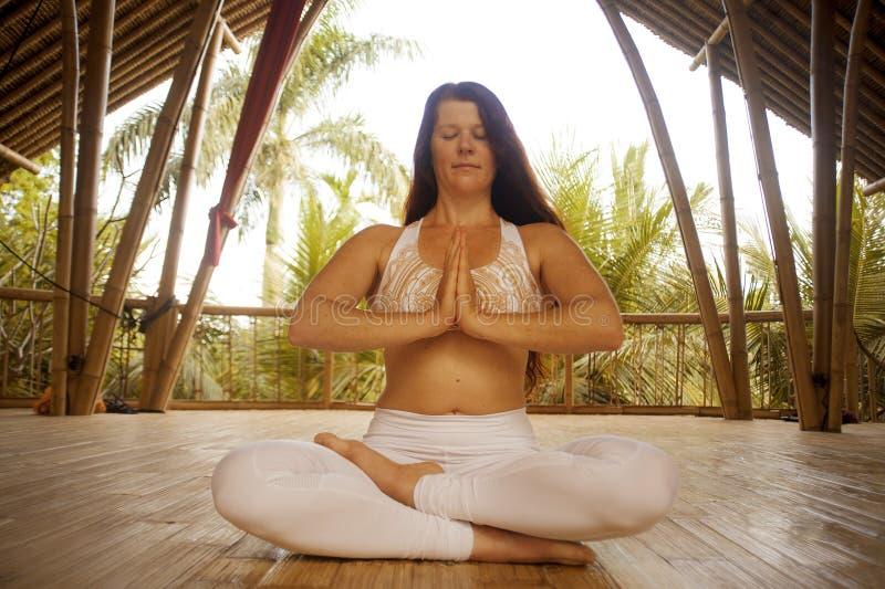 M?ody atrakcyjny, szcz??liwy zrelaksowany kobiety obsiadanie w lotosowej joga pozycji robi outdoors przy drewnian? bud? i fotografia royalty free