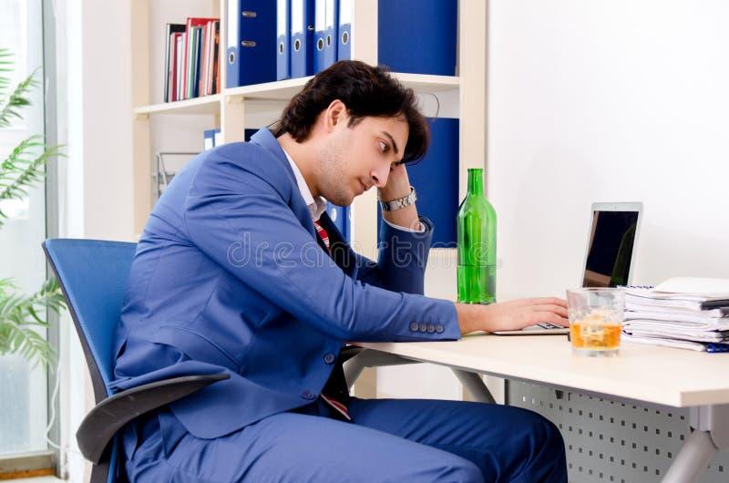 M?ody biznesmena pracownik pije w biurze obraz stock