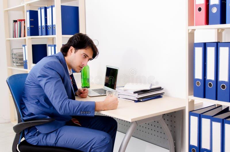 M?ody biznesmena pracownik pije w biurze zdjęcie stock