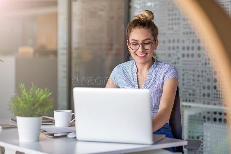M?ody biznesowej kobiety dzia?anie na laptopie w biurze zdjęcia stock