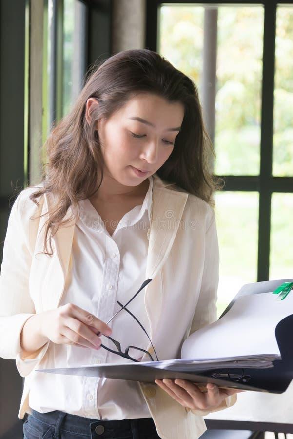 M?ody bizneswoman przy miejsce pracy i czytanie tapetujemy w biurze biznesowa kobieta jest ubranym kostiumu mienia dokumenty w r? zdjęcia royalty free