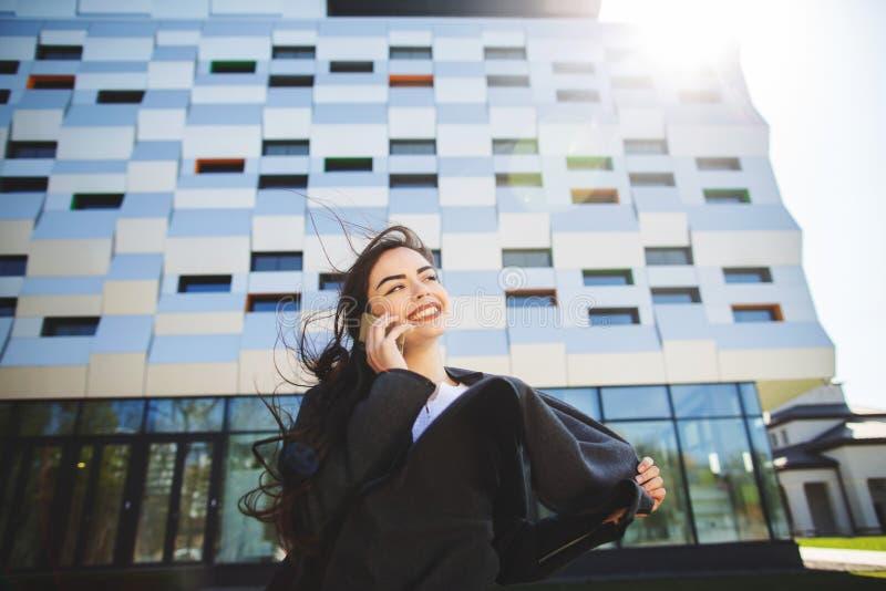M?ody bizneswomanu m?wienie na telefonie kom?rkowym podczas plenerowej kawowej przerwy blisko budynku biurowego, czarny komunikac obraz royalty free
