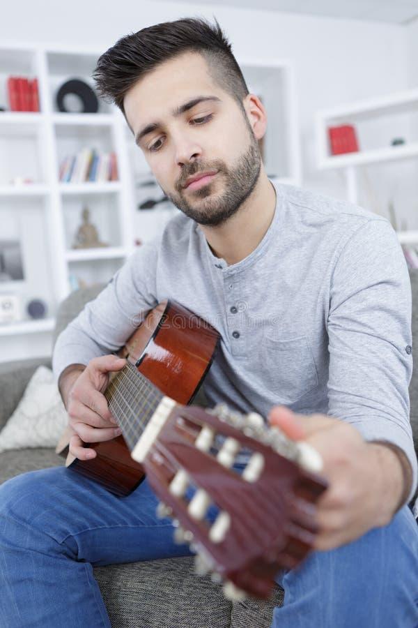 M?ody cz?owiek bawi? si? gitar? w domu zdjęcie royalty free