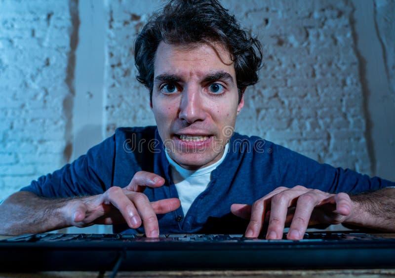 M?ody cz?owiek hacz?cy na komputerowym laptopie p??no przy nocy uczuciem stresuj?cym si? i bezsennym zdjęcie stock
